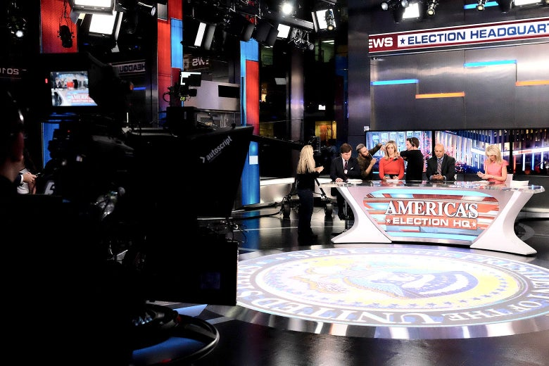 "Anchors and staffers prepare around a desk that is emblazoned with a sign that reads ""America's Election HQ."""