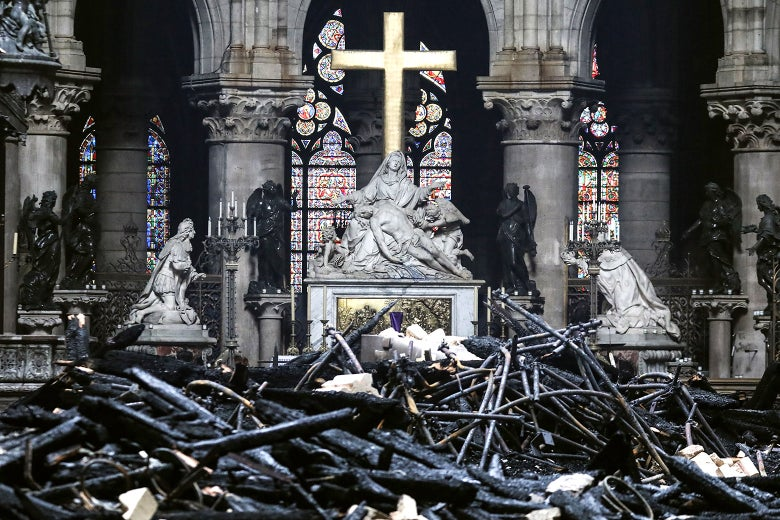 A statue on an alter with stained glass behind it, with burned rubble in front.