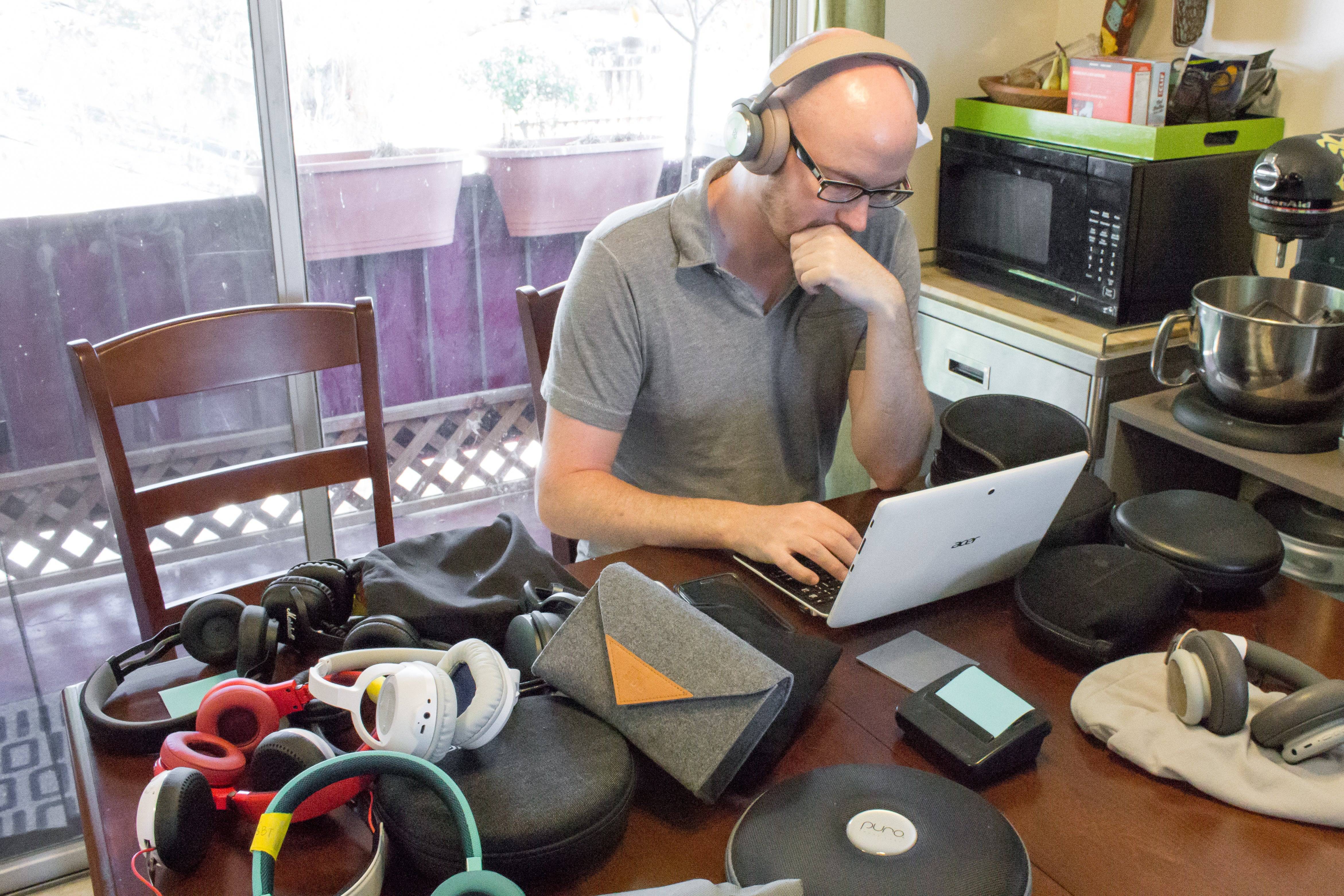 man working at his desk with a pile of headphones