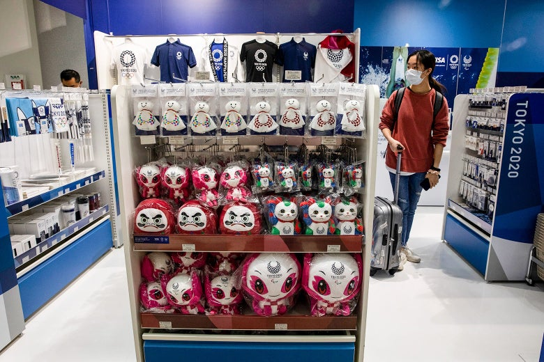 A traveler wearing a surgical mask walks by shelves full of Olympics souvenirs