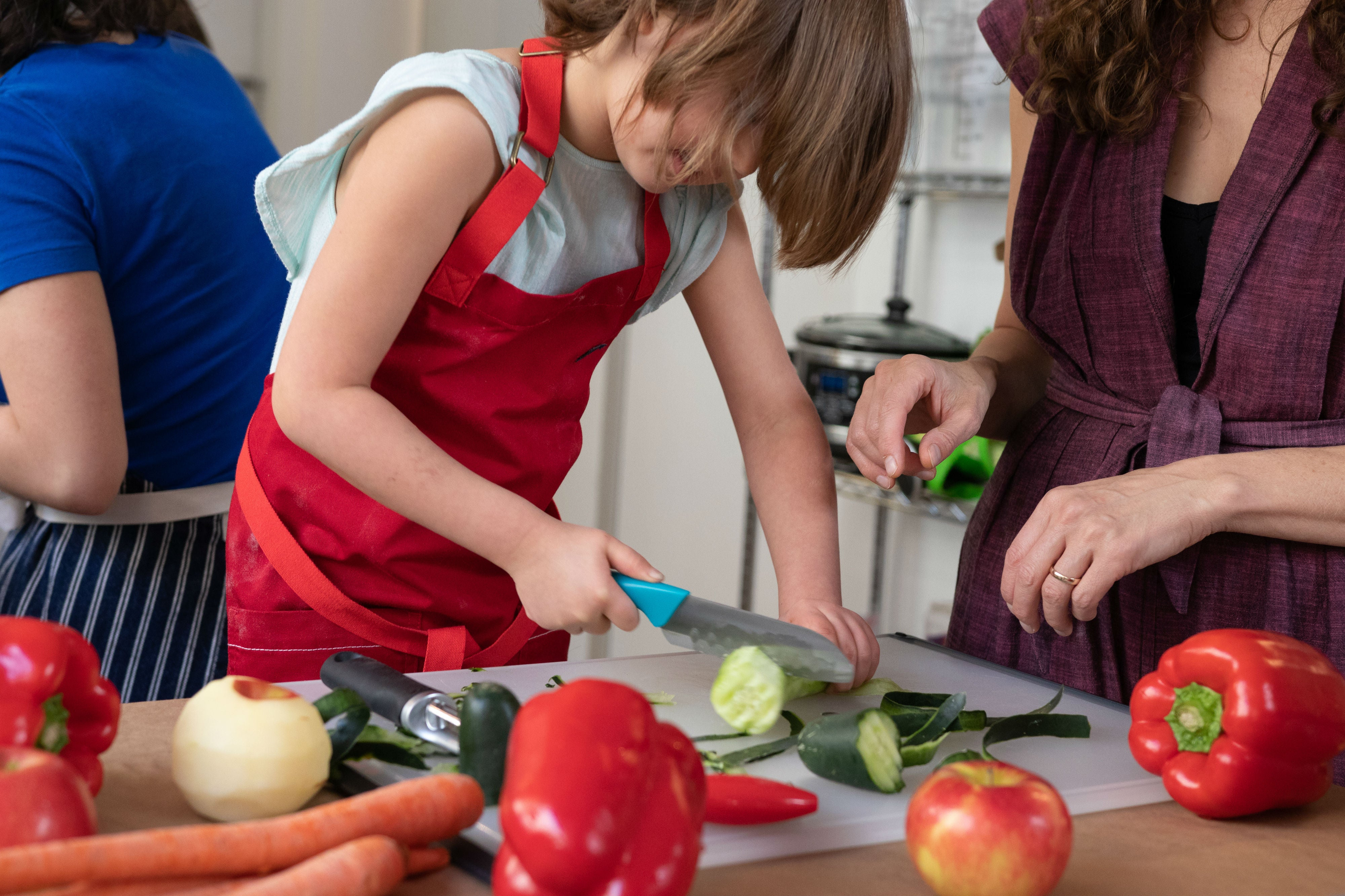 kid in apron chopping vegetables