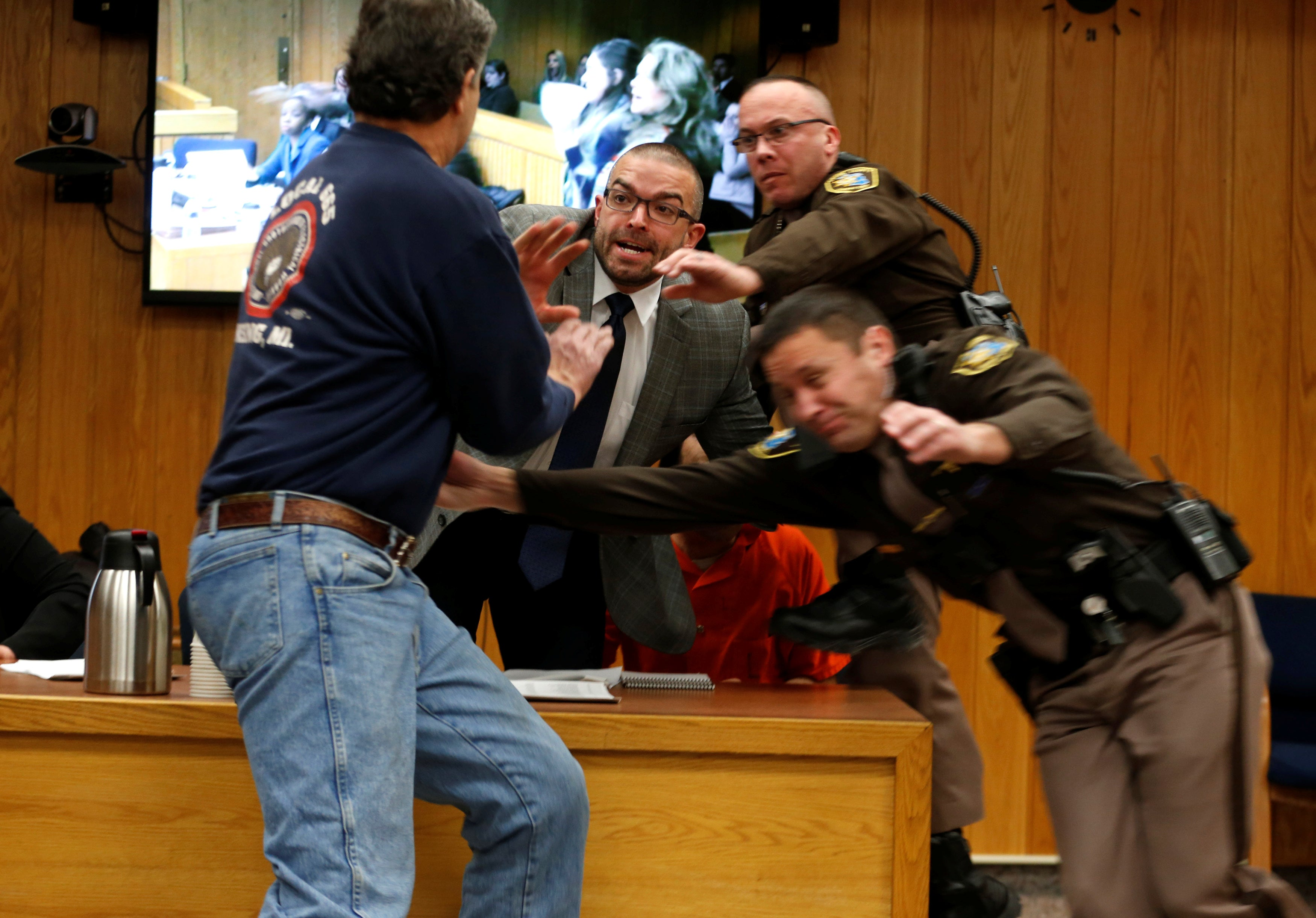 Randall Margraves (L) lunges at Larry Nassar (wearing orange), a former team USA Gymnastics doctor who pleaded guilty in November 2017 to sexual assault charges, during victim statements of his sentencing in the Eaton County Circuit Court in Charlotte, Michigan on February 2, 2018.