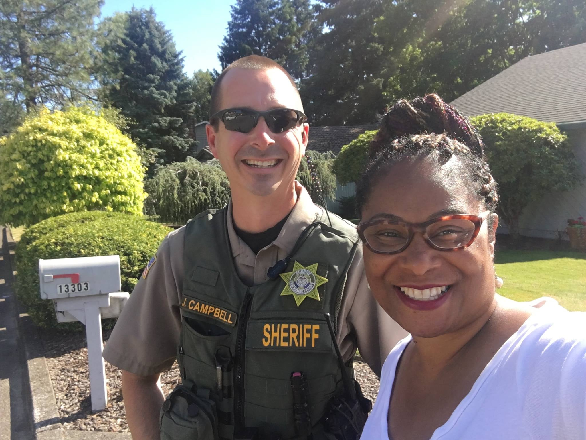A uniformed police officer bearing the name tag J. Campbell, smiling next to Janelle Bynum in front of a house.