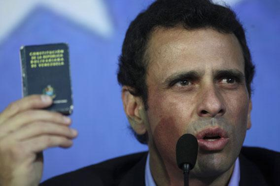 Opposition leader Henrique Capriles holds up a miniature copy of Venezuela's Constitution as he speaks during a press conference in Caracas, Venezuela, March 8, 2013.