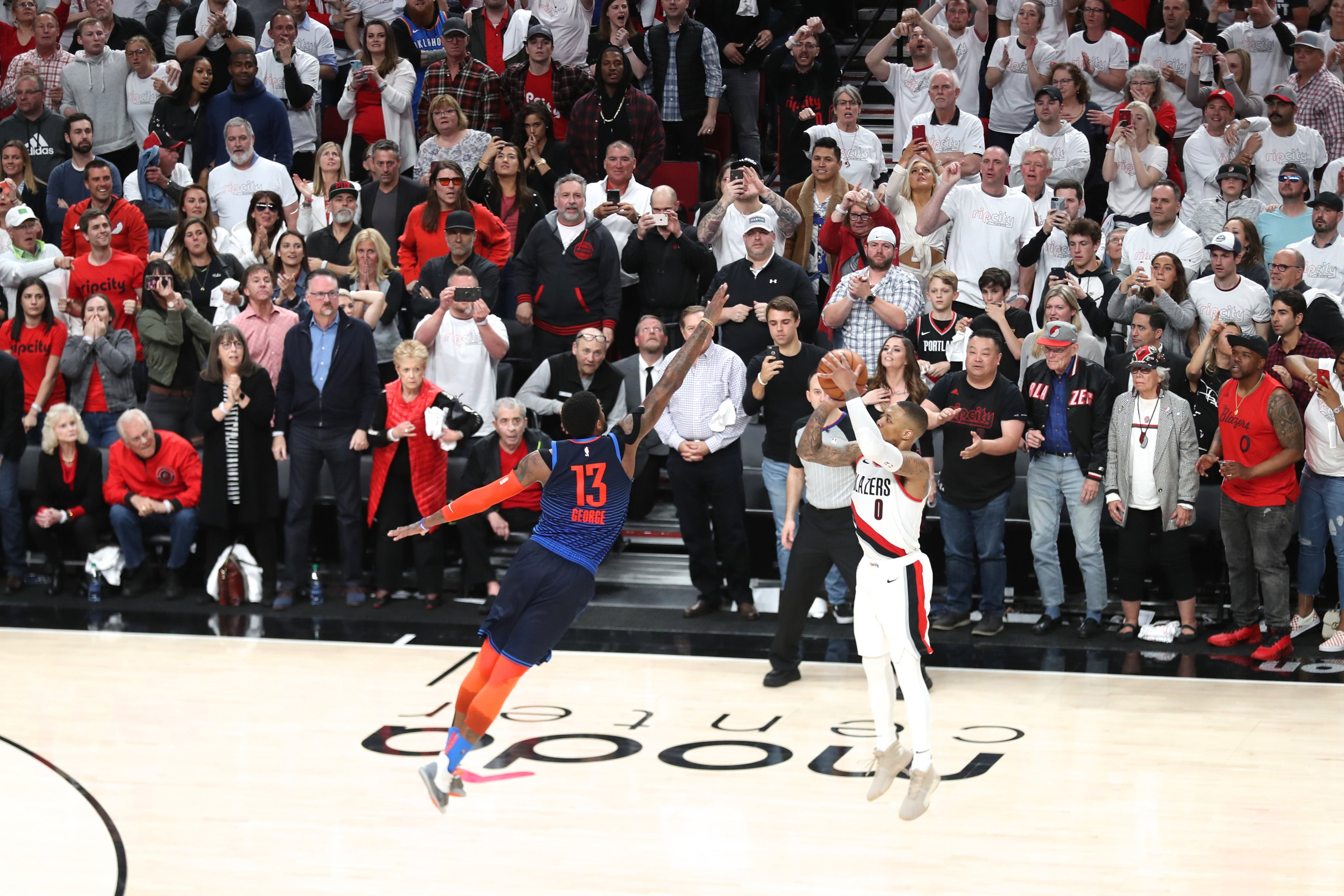 The Trail Blazers' Damian Lillard releases a 37-foot three-pointer over the Thunder's Paul George against a backdrop of intensely expectant fans.