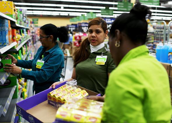 Walmart employee Yanetsi Grave and her fellow employees stock the shelves at a Walmart store on February 19, 2015 in Miami, Florida.