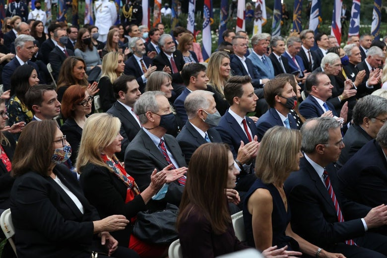 Rows of attendees, mostly maskless, seated closely together in the Rose Garden.