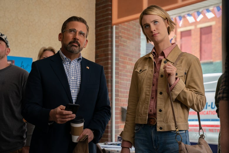Carell wears a blazer with an American flag pin and holds a smartphone and a to-go cup of coffee. Mackenzie Davis looks comfortable in blue jeans. Neither seems to be happy with what they're watching.