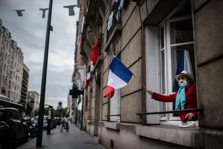 A woman wearing a mask leans out her first floor window and waves the French national flag to show support to healthcare employees.
