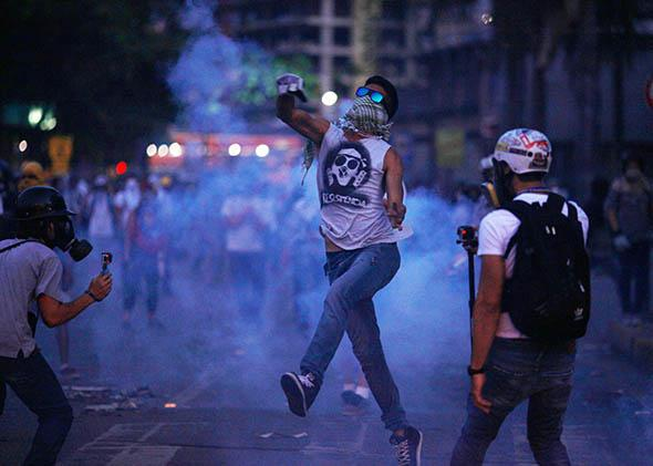 Opposition demonstrators are attacked with tear gas by riot police during a protest in Caracas on April 4, 2014.