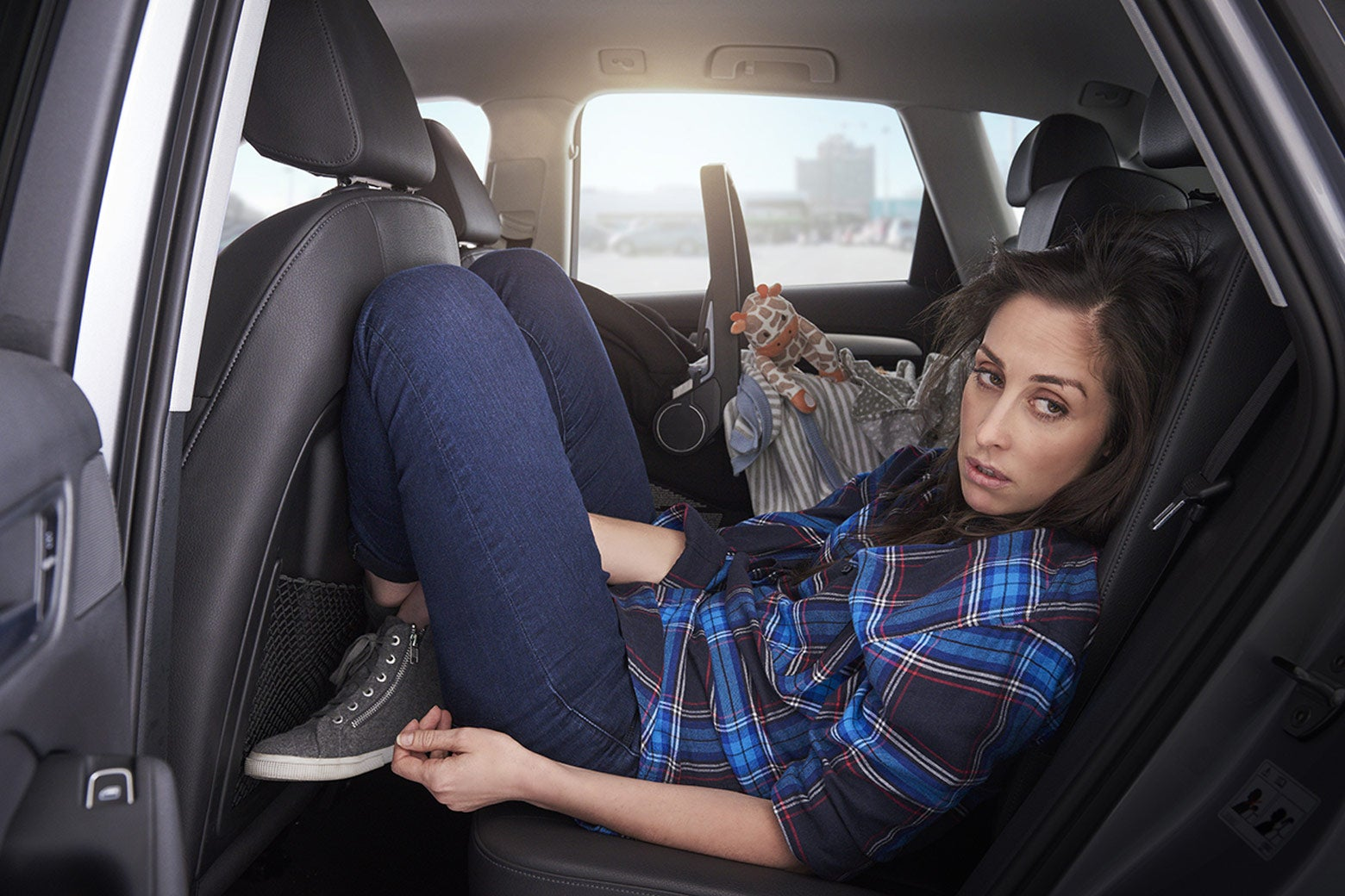 Catherine Reitman sits awkwardly in a car's rear, driver-side passenger seat in this still from Workin' Moms.