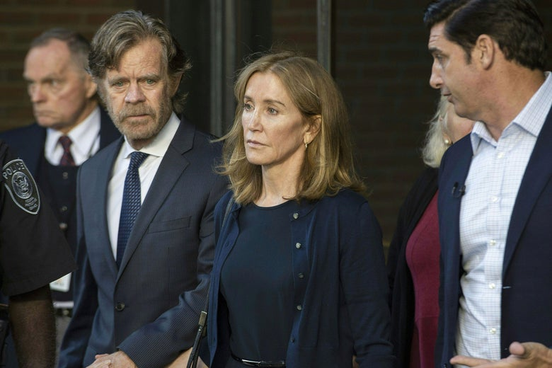 Actress Felicity Huffman is escorted by her husband, actor William H. Macy, out of the John Joseph Moakley United States Courthouse in Boston. They are wearing dress clothes.