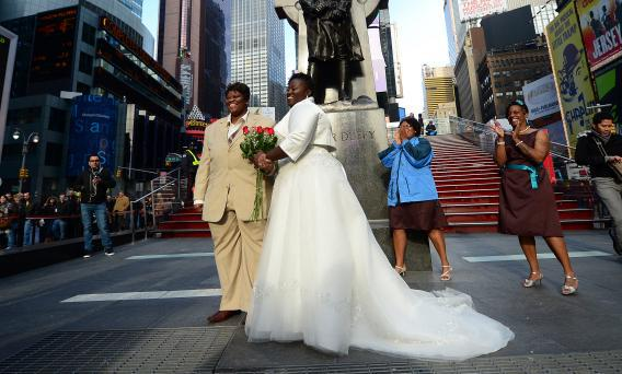 Chris, right, and Renee Wiley pose for a wedding photo on Times Square in New York.
