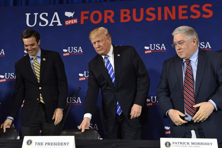 US President Donald Trump(C) arrives for a round table discussion on tax reform, at White Sulpher Springs Civic Center in White Sulpher Springs,West Virginia on April 5, 2018.          Shown to his left is Rep. Evan Jenkins, and (R)West Virginia Attorney General Patrick Morrissey.   / AFP PHOTO / Nicholas Kamm        (Photo credit should read NICHOLAS KAMM/AFP/Getty Images)