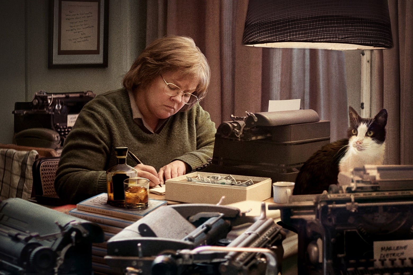 In a scene from Can You Ever Forgive Me? Lee Israel, played by Melissa McCarthy, sits at a desk forging a letter. There are several typewriters, a lamp, and a cat on the desk.