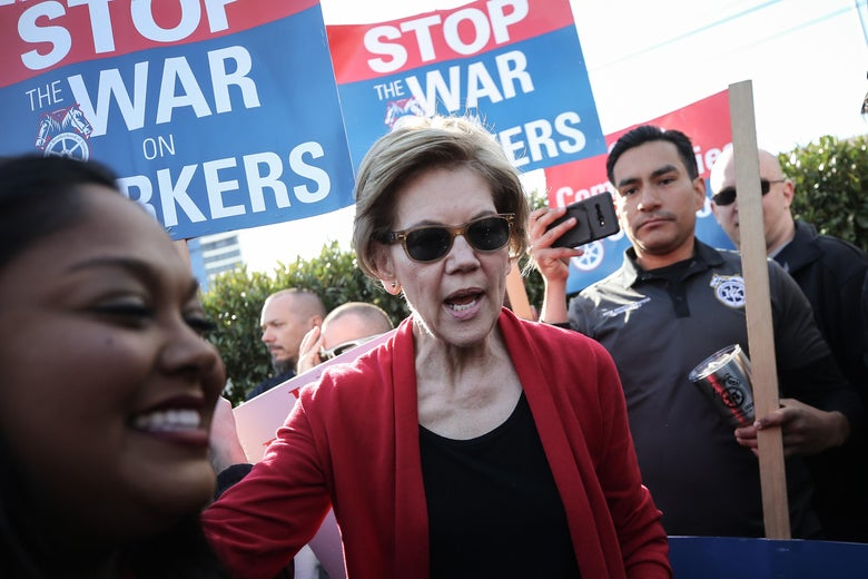 Sen. Warren in sunglasses marching, chanting, and carrying a picket.