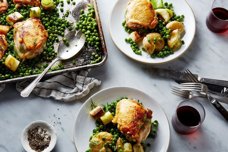 A baking dish filled with baked chicken and peas peeks in from the top left corner. Two white plates of chicken with vegetables sit on a white marble countertop, laden with silverware and glasses of wine.