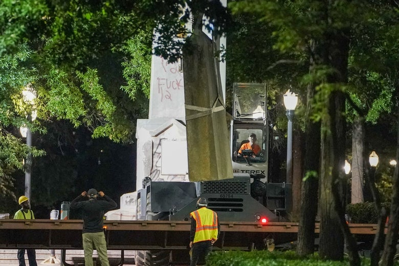 Construction workers with large machinery examine a graffiti-covered white obelisk.