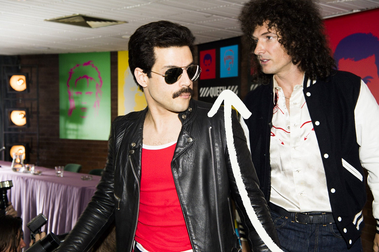 Scene from Bohemian Rhapsody with Hot Space album art in background
