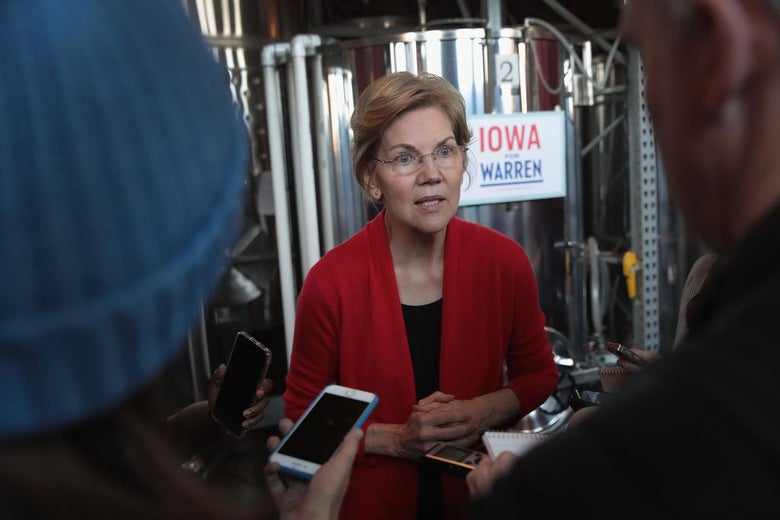 Warren, wearing a red blazer, speaks to two reporters while standing in front of a big old vat of wine.