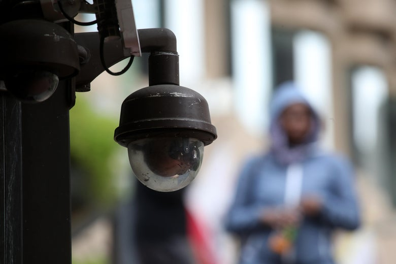 A close-up shot of a surveillance camera, with a pedestrian in a blue hoodie in the background.