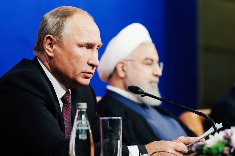 Vladimer Putin talking into a mic at a press table with Hassan Rouhai.