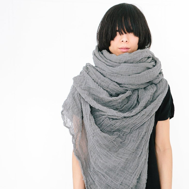 A woman wearing a Scarf Shop cotton giant scarf