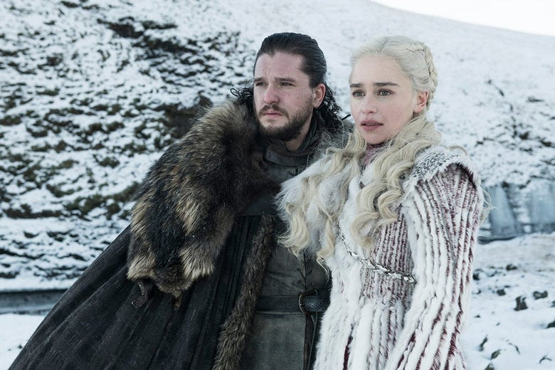 Kit Harington and Emilia Clarke, dressed in fur, stand in front of a snowy mountain landscape.