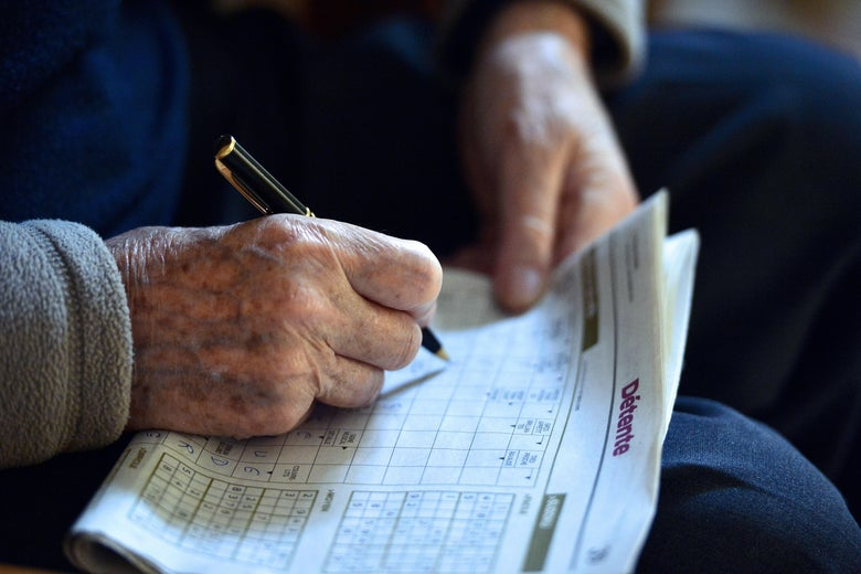 An elderly man fills in the crossword prior to Christmas eve dinner on December 24, 2014, at the St. Joseph retirement home in Nantes.