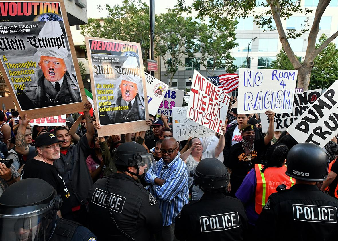 Protesters hold up signs against a police skirmish line near where Republican presidential candidate Donald Trump holds a rally in San Jose, California on June 02, 2016.