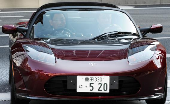 Toyota Motors President Akio Toyoda (L) and Tesla Motors CEO Elon Musk drive a Tesla Roadster in 2010. Both companies have separate plans for computerized driving-assistance technology.