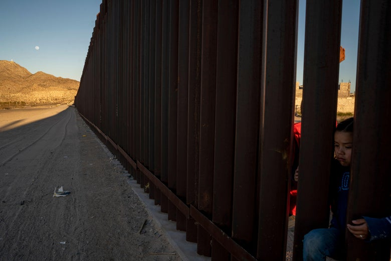 A young  girl is pictured on the between the metal fencing on the US-Mexico border on March 19, 2019.