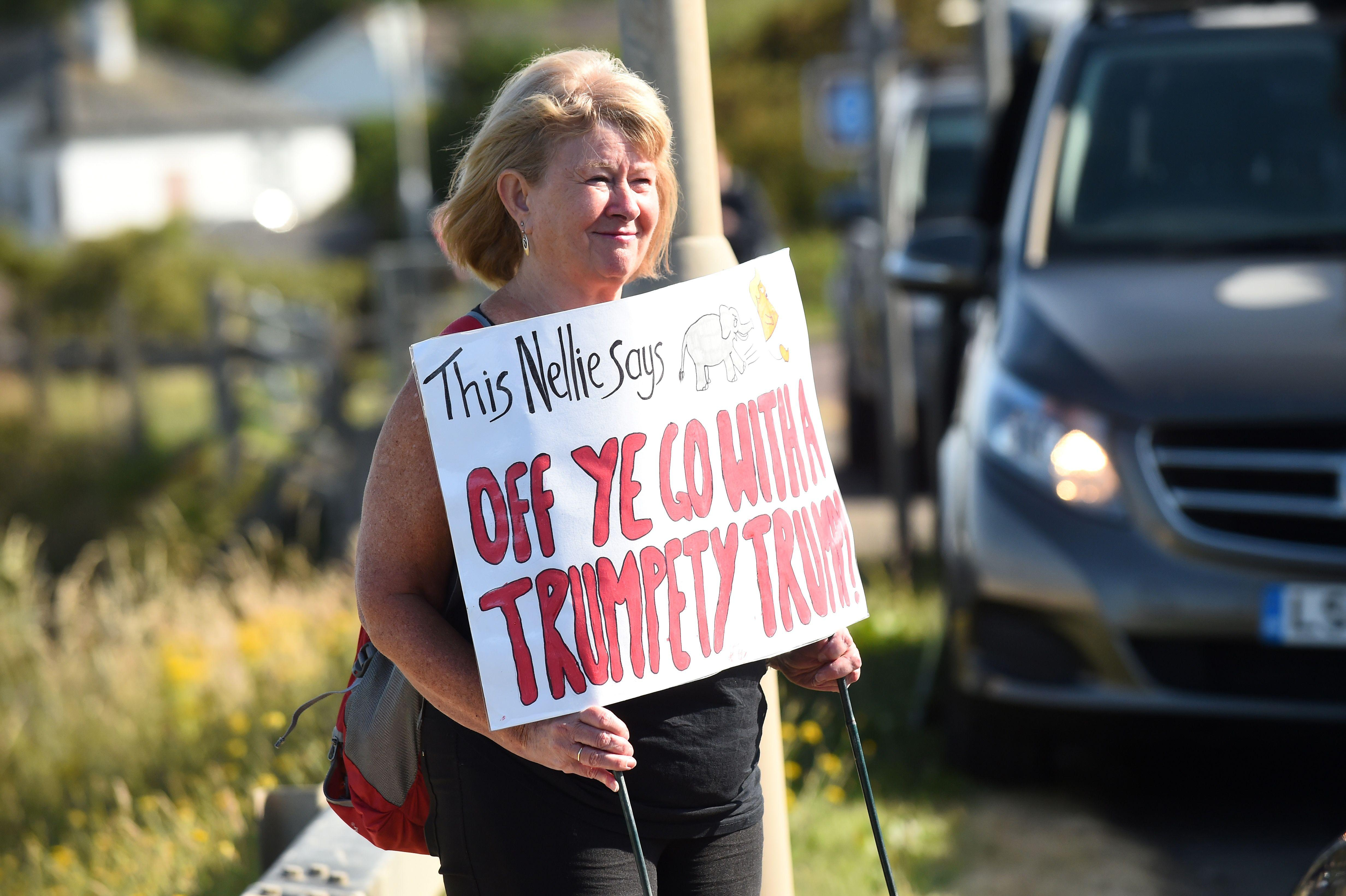A protestor against the UK visit of US President Donald Trump holds a placard outside Trump Turnberry, the luxury golf resort of US President Donald Trump, in Turnberry, southwest of Glasgow, Scotland on July 14, 2018.