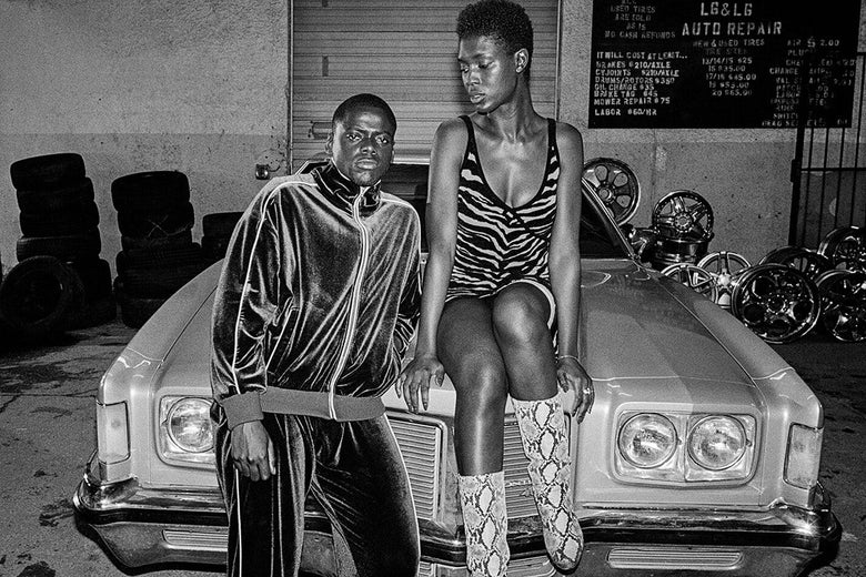 A black-and-white photo of Daniel Kaluuya and Jodie Turner-Smith on the hood of a car.