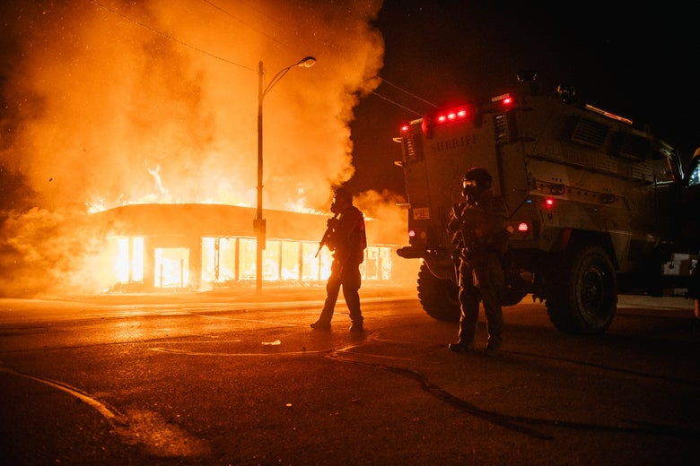 A police armored vehicle patrols an intersection with a building on fire in the background.