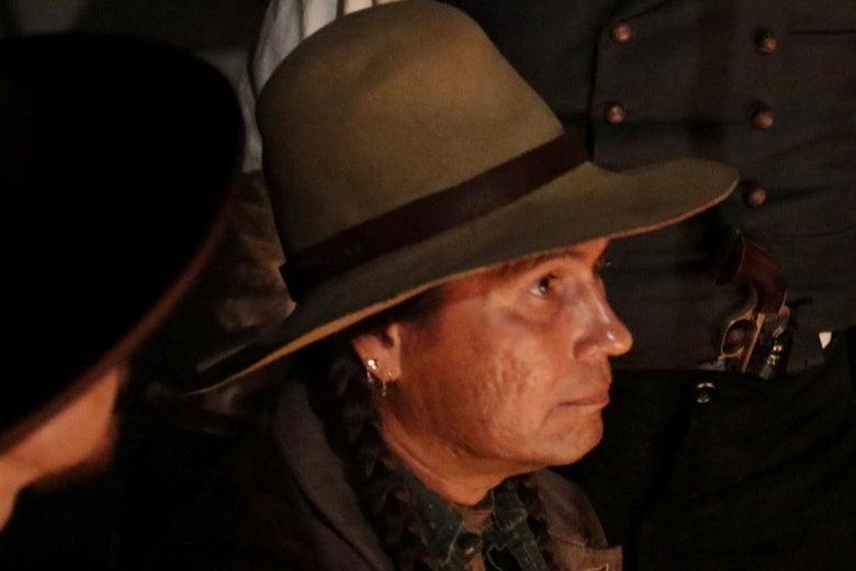 Mo Brings Plenty portraying Ottawa Jones wearing a hat and sitting by a fire.