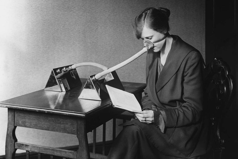 A woman sits at a table wearing a mask over her nose that is connected to a metal device via a series of tubes