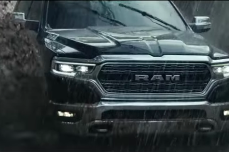 A Ram truck drives through mud.