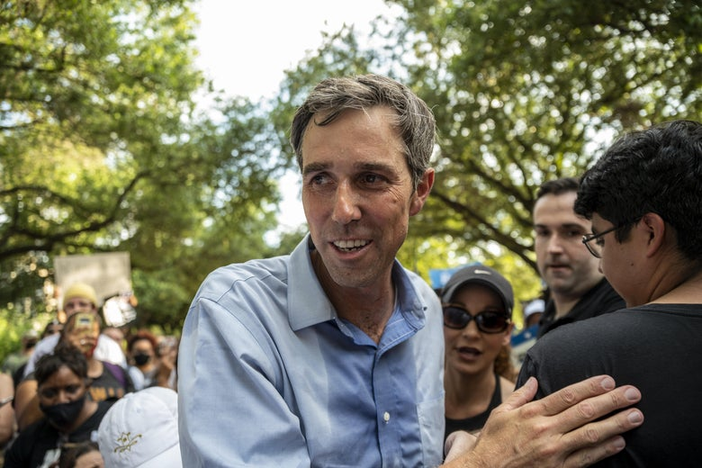 Beto in a button-down drenched in sweat smiles and pats someone's back as he walks through a crowd in a tree-lined area