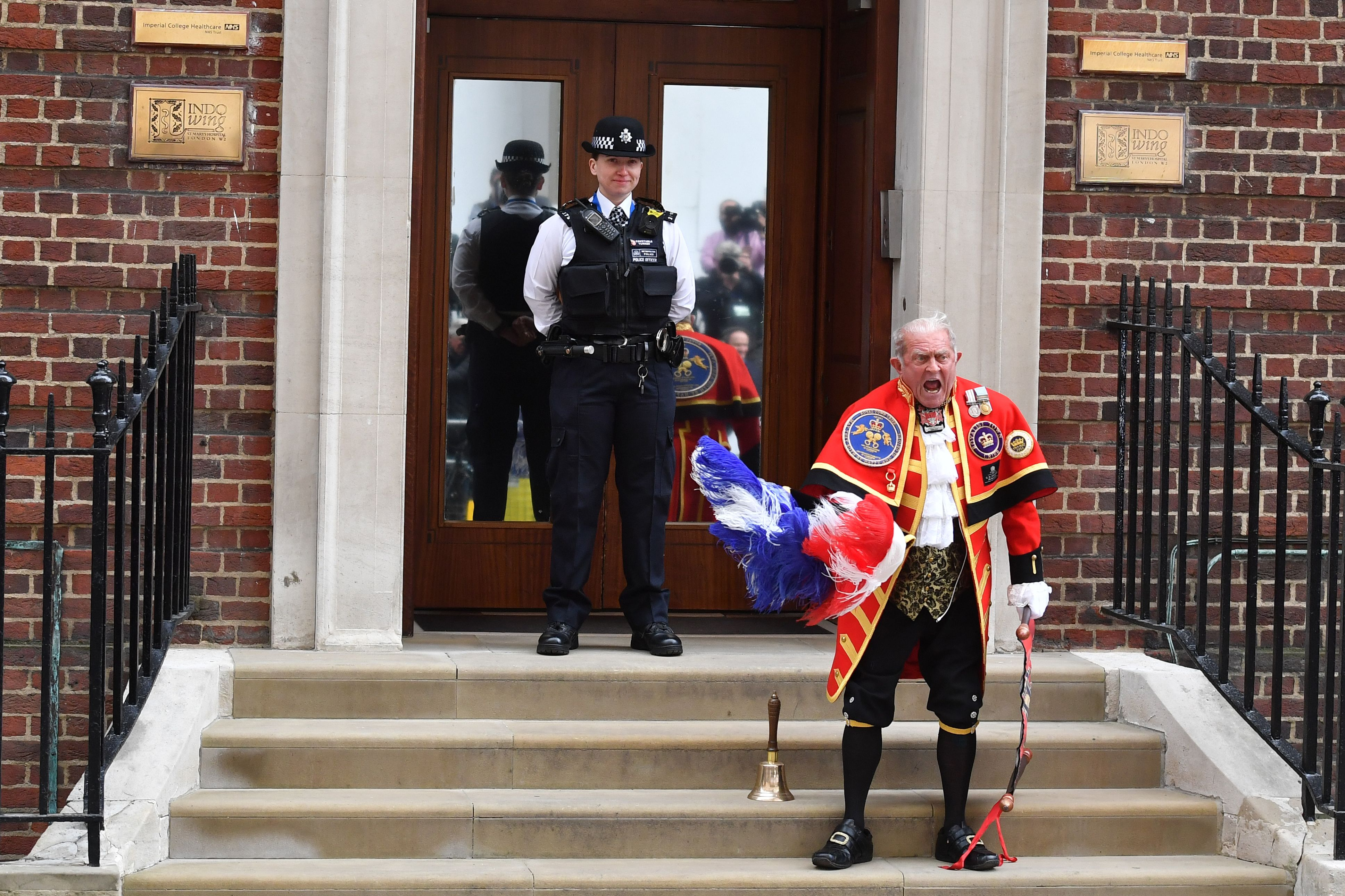 A town crier reads the news of the royal birth.