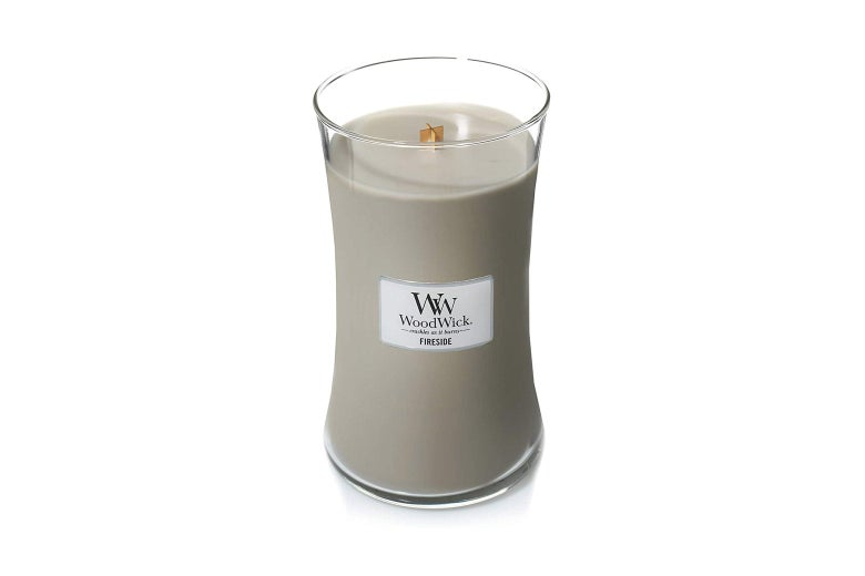 A cream-colored WoodWick candle.