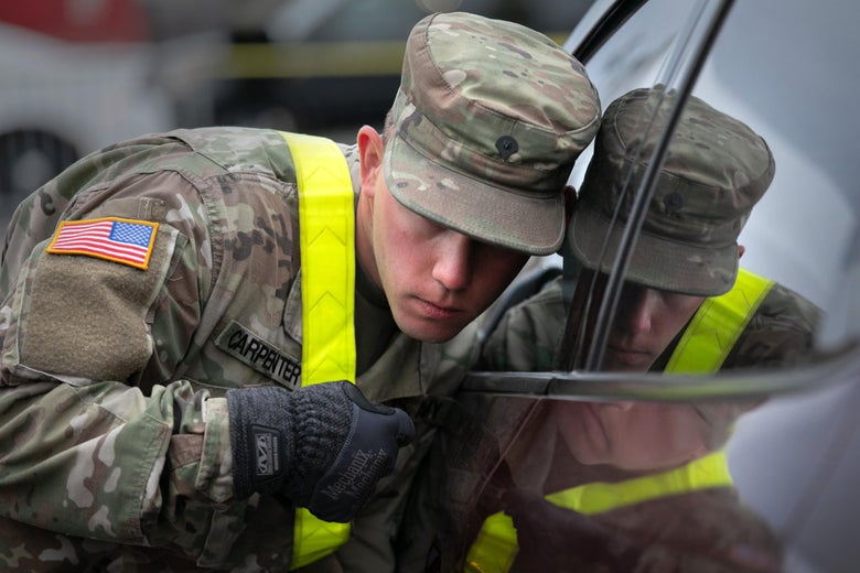 A U.S. National Guard soldier listens to a patient at a drive-thru coronavirus testing center at Lehman College on March 28, 2020 in the Bronx, New York City.