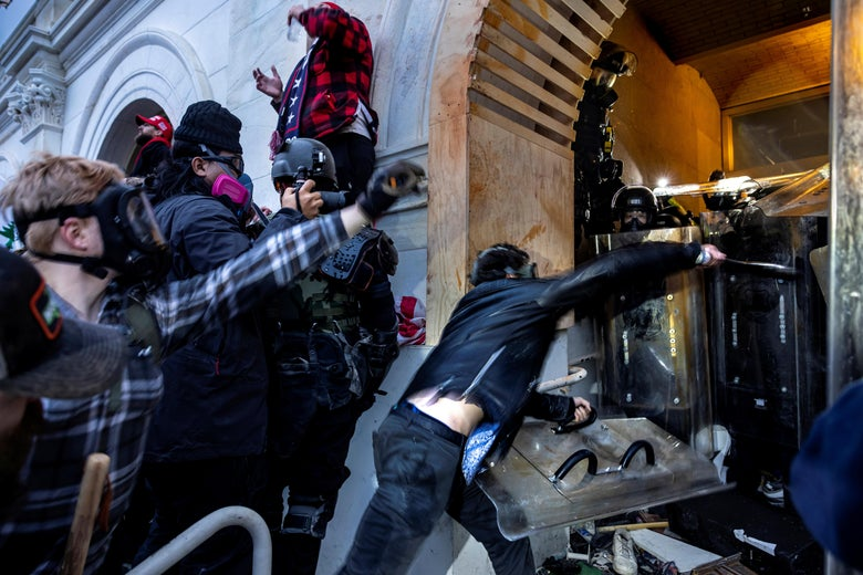Masked rioters assault law enforcement officers at an entryway to the Capitol.