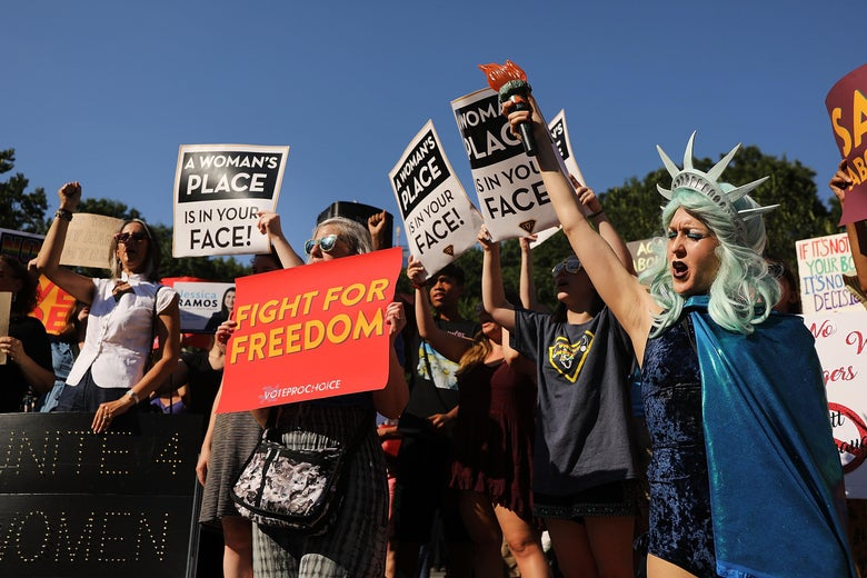 """A group of protesters stand holding signs that say """"A woman's place is in your face,"""" and """"Fight for freedom."""""""