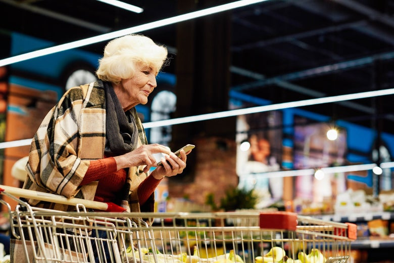 An older woman uses a smartphone while she pushes a shopping cart.