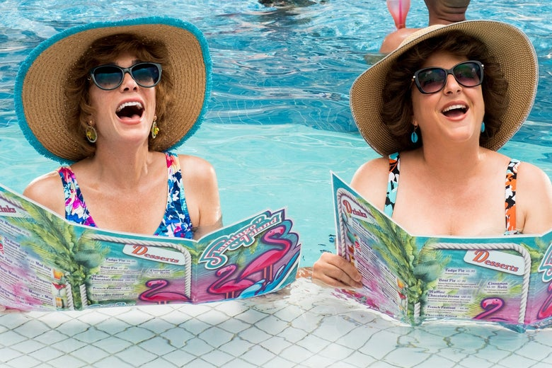 Two women with sunglasses are reading magazines in a pool and smiling.