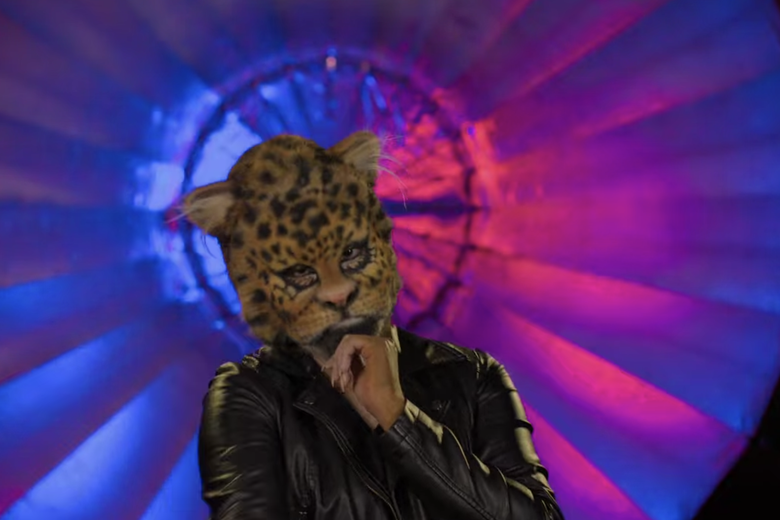 A woman in a brown jacket with a leopard head.
