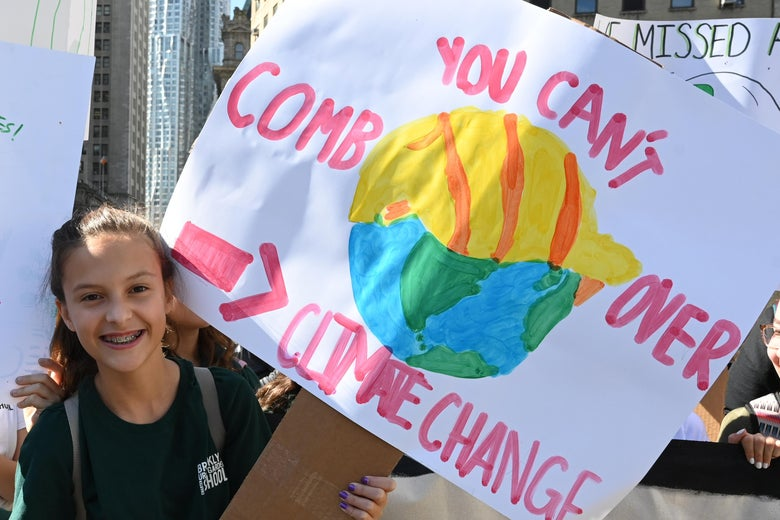 "A student holds up a sign that says ""you can't comb over climate change."""