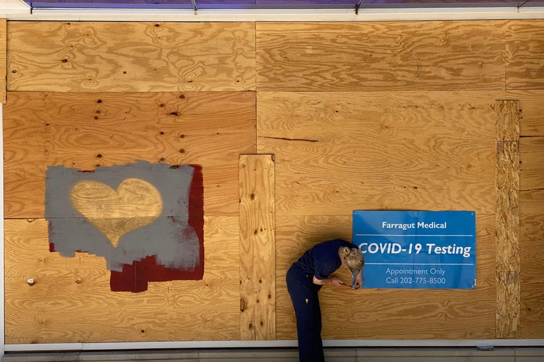 A woman puts up a sign for COVID-19 testing on a boarded-up wall