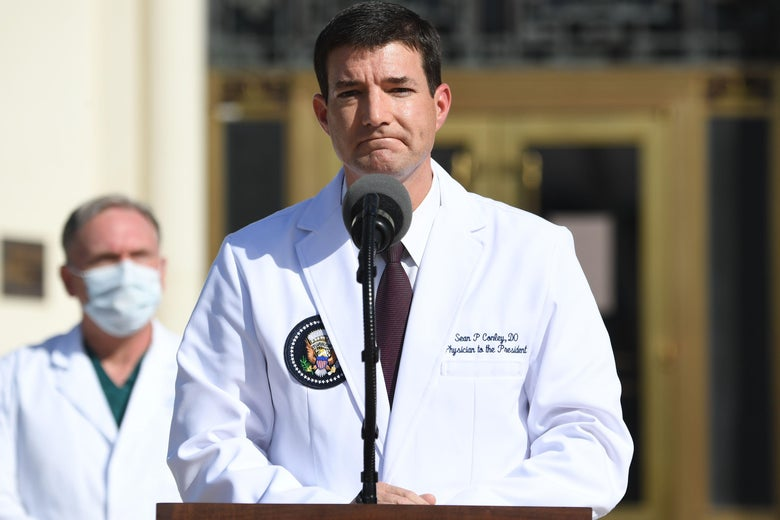 A man in a white coat at a lectern frowns.